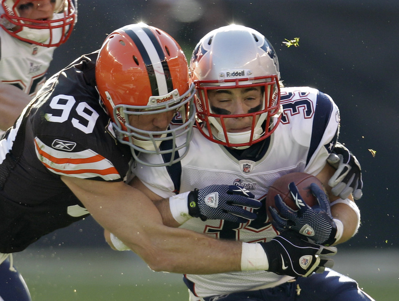 Linebacker Scott Fujita stops running back Danny Woodhead of the Patriots after a 6-yard run in the second quarter Sunday in Cleveland. The Browns surprised the Pats with a 34-14 win.