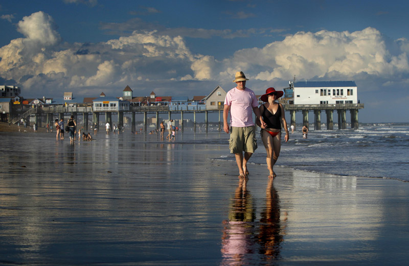 In this Aug. 26, 2010, photo, Dan Horner, left, and Cynthia Belaskie, of Toronto, stroll along the ocean in Old Orchard Beach.