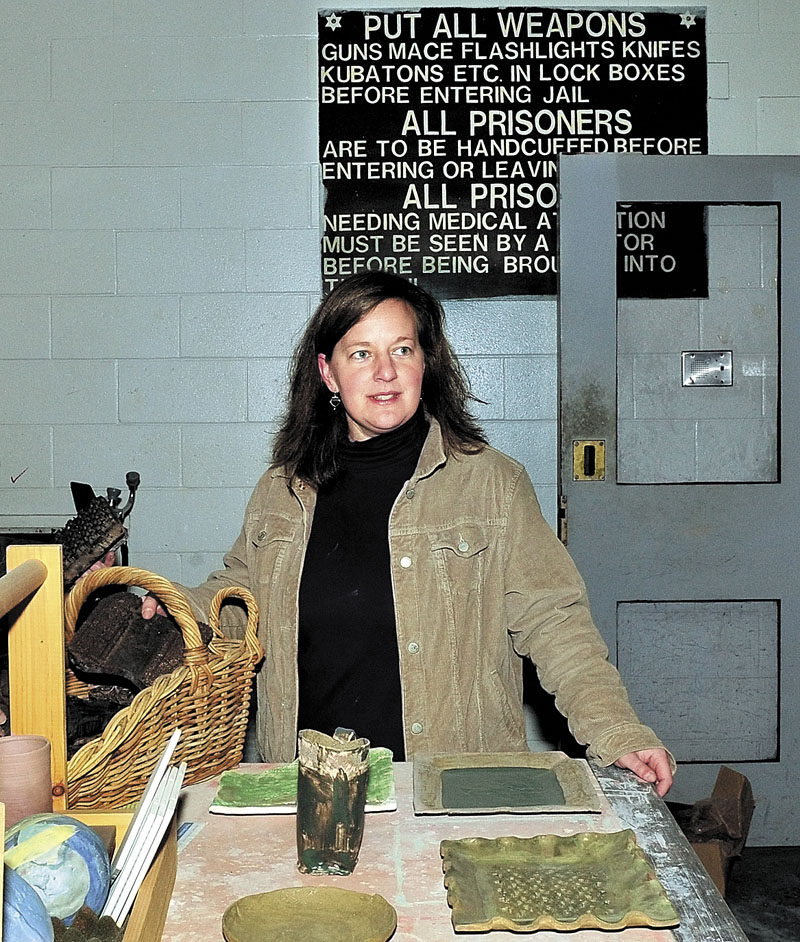Amber Lambke, owner of Somerset Grist Mill in the former Somerset Jail in Skowhegan, speaks about a pottery venture in the sally port where prisoners were transported and a sign in background advised jail personnel to remove their weapons before entering jail.