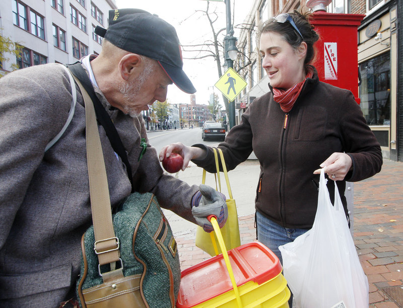 Andrea Parker of Portland gives an apple to Philip Champagne on Sunday as part of a pay-it-forward event in Monument Square.