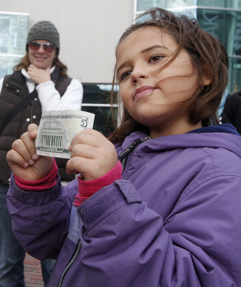 Sia Hyson, 7, of Gorham tries to decide what to buy to brighten other people's lives with the $5 her mom gave her.
