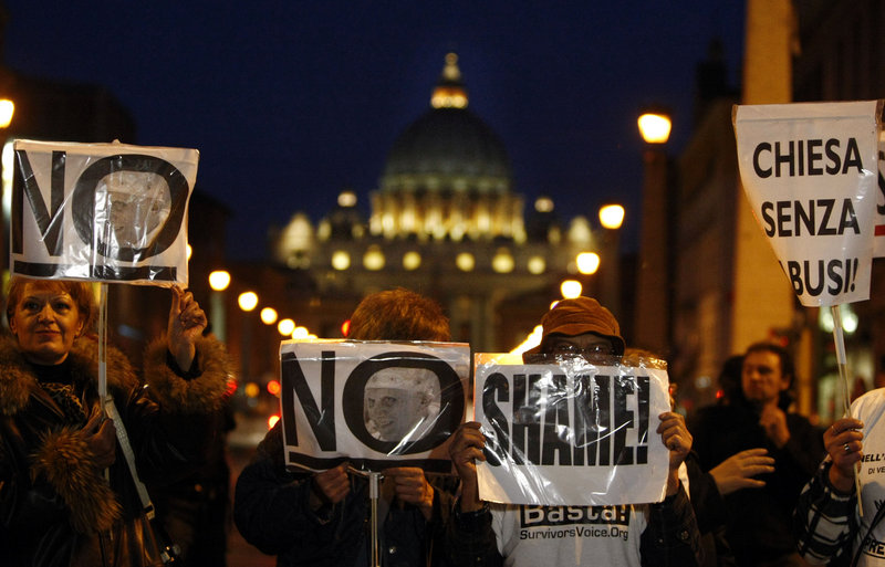 Demonstrators hold placards Sunday in Rome. Italian paramilitary police blocked a boulevard to prevent a march by sex-abuse survivors from reaching St. Peter's Square.