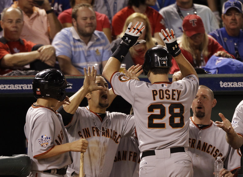 Buster Posey is congratulated by his teammates after hitting a solo home run in the eighth inning to give the Giants a 4-0 lead. San Francisco needs a win tonight to finish the series.