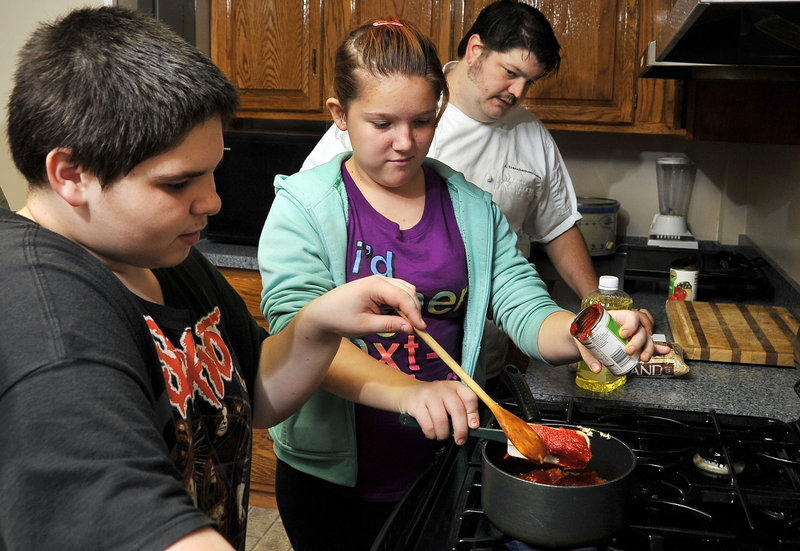 """Chef James Tranchemontagne of the Frog and Turtle and the French Press Eatery restaurants in Westbrook says being involved in the Cooking Matters program is """"like a dream come true."""" Here he looks on as Corey Watson, 13, and Kristen Wiggins, 12, work on a marinara sauce. Below, Tranchemontagne and Amber Weitzell, 12, add the onions."""