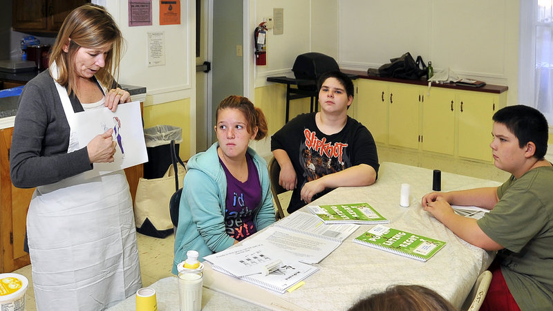 Brenda Bracy shares her knowledge of nutrition with Kristen Wiggins, 12, Corey Watson, 13, and Stephen Foster, 11.