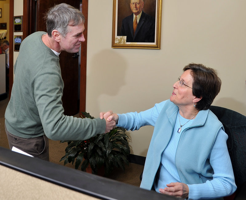 Visting businesses in his hometown of Gorham on Monday, Shawn Moody shakes hands with Patsy Waterman, an agent with the Chalmers Insurance Group on Main Street.