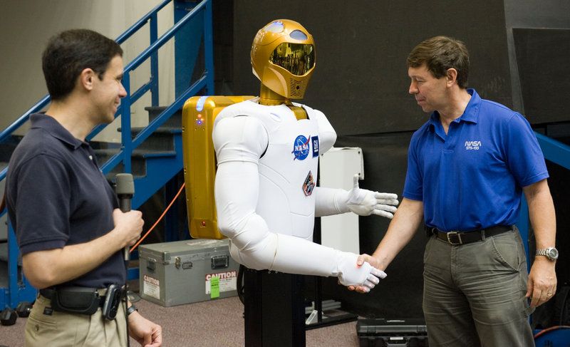 NASA astronaut Michael Barratt shakes hands with Robonaut 2 during a news conference in the Space Vehicle Mock-up Facility at the Johnson Space Center in Houston.