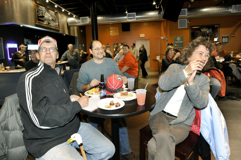 Charlie Morse of Gray, left, and Nick and Angie Palestini of Portland cheer Maine's picks at Binga's Wingas in Portland while watching the NBA Development League draft Monday.