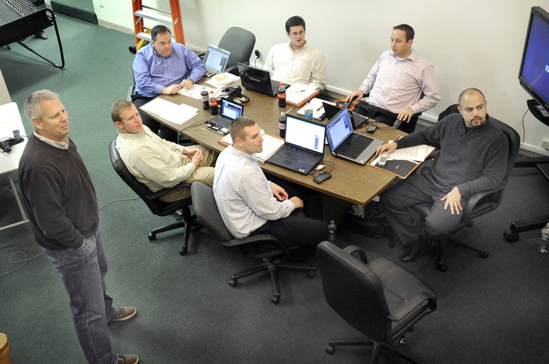 Celtics President Danny Ainge, standing, oversees the Red Claws draft Monday night at the club's offices. Maine GM Jon Jennings is at the left end of the table. Seated, clockwise, are Chris Sellos, Coach Austin Ainge, Hernando Planells, Cam Twiss and Jay O Connell.