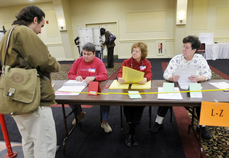 Election clerks Gail Hannon, left, Erlene Stuart and MaryAnn Morin are ready to check in voters, including Cory Lasala, far left, at the Italian Heritage Center in Portland on Tuesday.