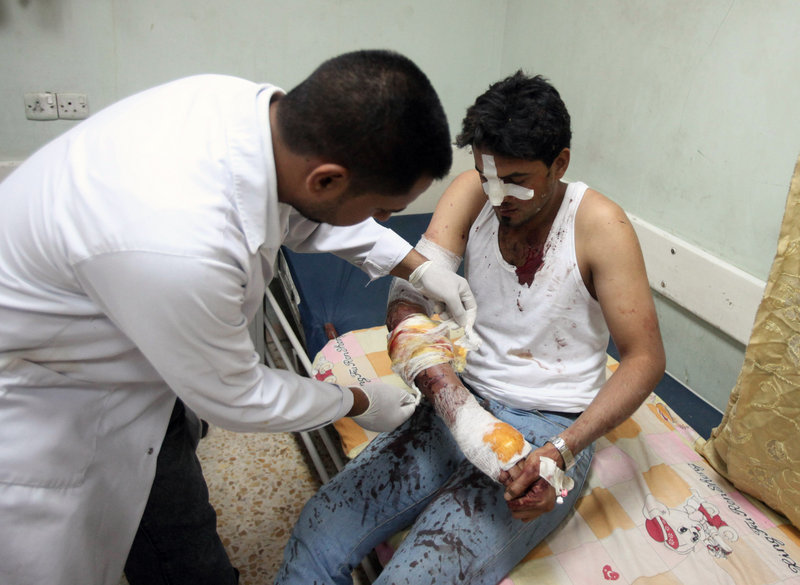 A wounded man is treated after a bombing in the Shiite neighborhood of Sadr City in Baghdad on Tuesday. Rapid-fire bombings and mortar strikes in mostly Shiite neighborhoods of Baghdad killed up to 76 and wounded hundreds, increasing doubts about the ability of Iraqi security forces to protect the capital.