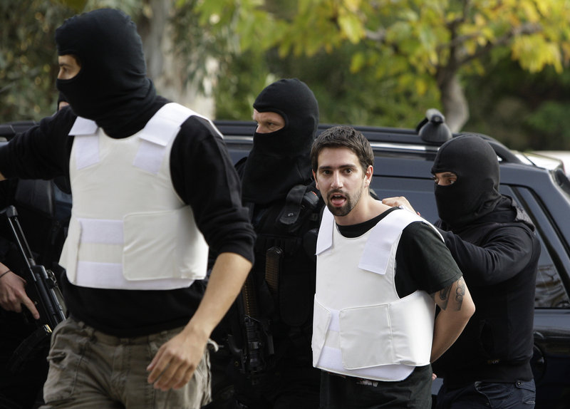 Police escort a man to a public prosecutor's office in Athens on Tuesday. Eight embassies in Athens were the intended targets of mail bomb attacks Monday and Tuesday. French President Nicolas Sarkozy was also targeted with a package that was intercepted.