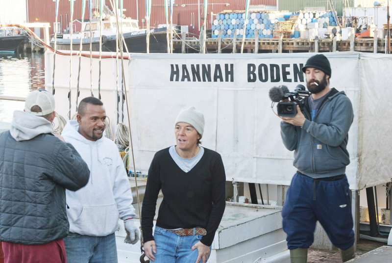 Linda Greenlaw, center, who captains the Hannah Boden, speaks to members of her crew after docking the sword boat at the Portland Fish Exchange on Wednesday morning. A Discovery Channel videographer, right, records the scene.