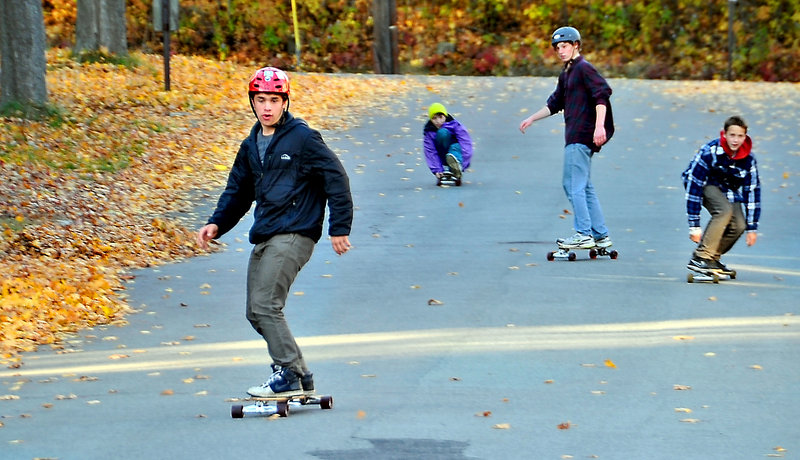 Oliver Nolan, 14, leads the pack as he and friends enjoy the colorful autumn weather to skateboard down a quiet neighborhood street in Portland near the Brighton campus of Maine Medical Center. Boarding with him are, left to right, Isaac Santerre, 14, Zack Roland, 14, and Dana Kuniholm, 15.