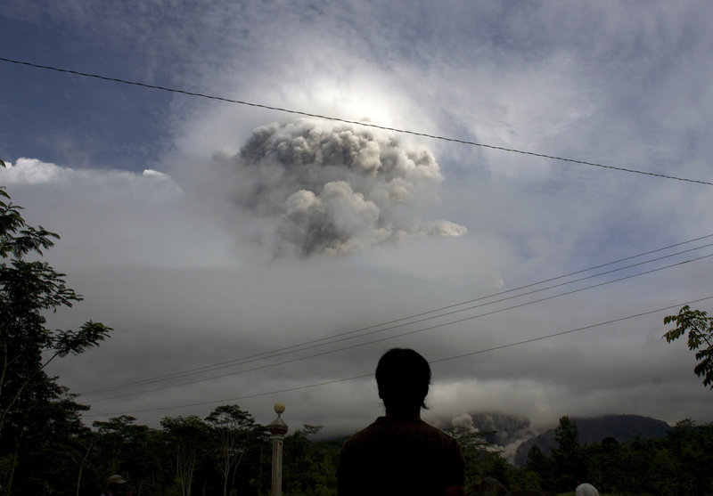 A man watches Wednesday as Mount Merapi erupts in Indonesia. The country is prone to volcanic activity because it sits along a string of faults in the Pacific Ocean region.