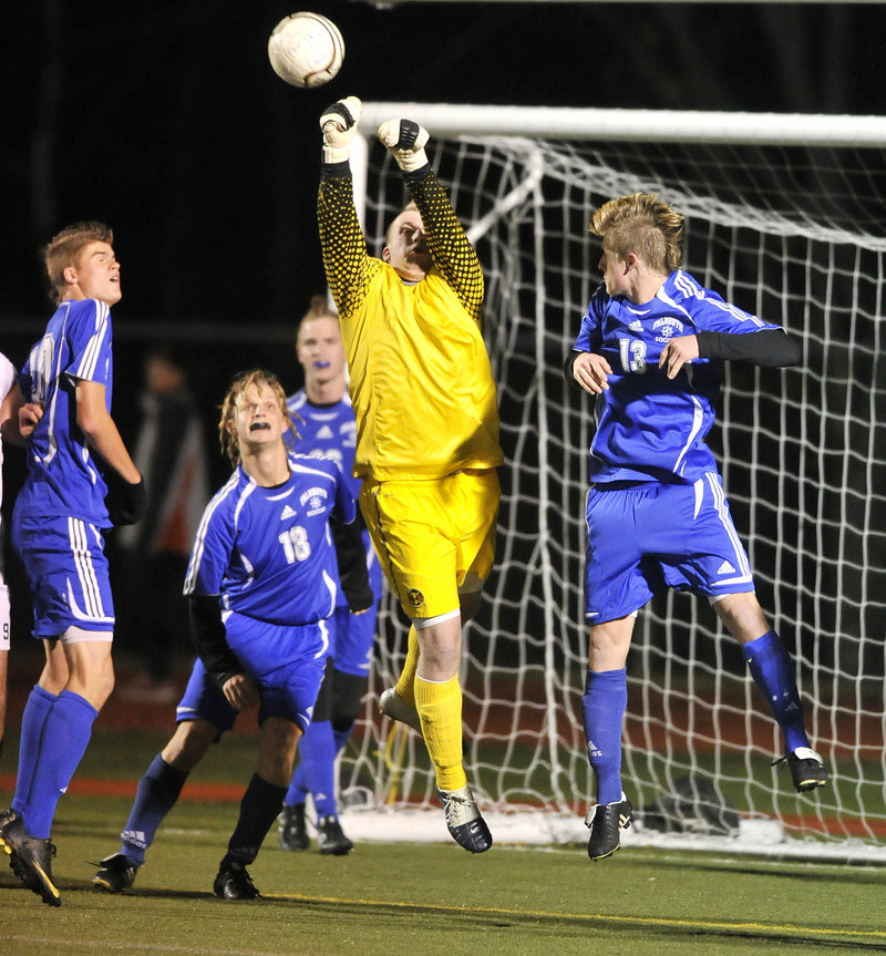 Falmouth goalie Ben Goffin, surrounded by his defense, knocks away a Yarmouth corner kick Wednesday night. Yarmouth won the Western Class B title with a 1-0 overtime victory.