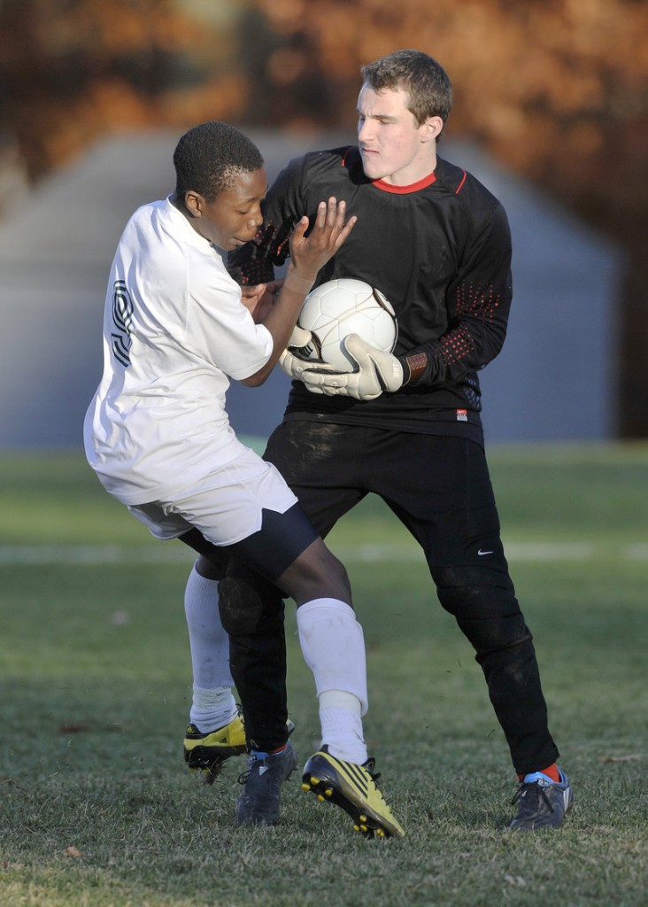 NYA goalie Jordan Haskell keeps the ball away from Kevin Kanakan of Waynflete, who stopped short to avoid a collision. NYA won Western Class C, 1-0.