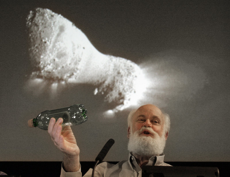 Michael A'Hearn uses a plastic bottle to describe the rotation of the comet Hartley 2 beneath an image made from NASA's Deep Impact spacecraft, which passed within 435 miles of the comet, at the Jet Propulsion Laboratory in Pasadena, Calif., on Thursday.