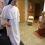 Andrea Bowers, 16, kneels in the hallway of the chapel at Spiritus Sanctus Academy in Ann Arbor, Mich., as members of the Dominican Sisters of Mary, the order that runs the school, proceed to receive communion during Mass. In sharp contrast to many other congregations, the conservative order is growing rapidly, and the average age of its 113 members is 26.