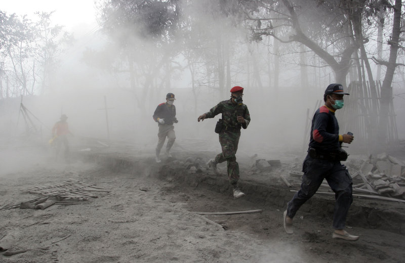 An Indonesian solder and rescuers run after an eruption of Mount Merapi in Indonesia on Friday. The danger zone has been expanded to a ring 12 miles from the mountain's peak.