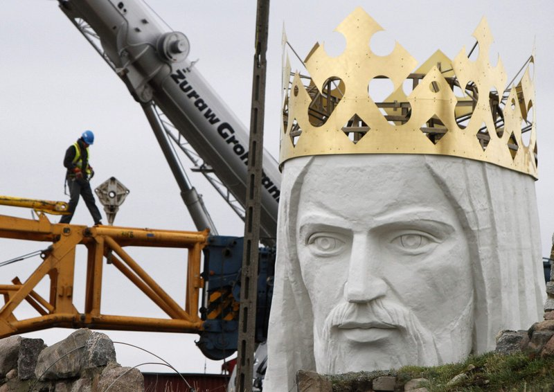Workers struggle against the wind Friday to assemble a crane that is to lift the 32-ton head and shoulders atop a giant concrete and metal statue of Jesus in Swiebodzin, Poland. Another effort to complete the project will take place today.