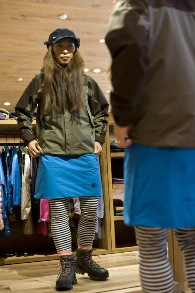 Minako Yoshikoshi, who works at Tokyo's North Face Harajuku store, tries on clothes popular with the growing number of women who are taking to the hills of Japan wearing short pants or fleece skirts with leggings and designer trekking boots.