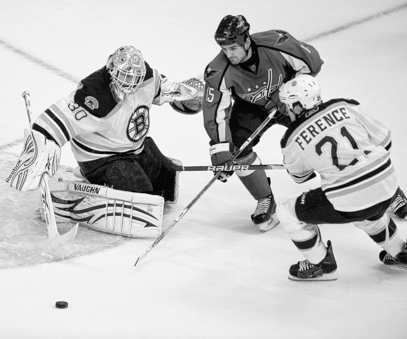 Washington's Boyd Gordon works for the puck against Boston goalie Tim Thomas and defenseman Andrew Ference. The Capitals overcame a Bruins rally to win 5-3 Friday.