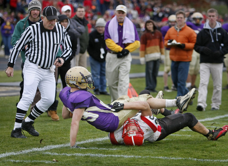 Jack Bushey of Cheverus is dragged down by Scott Thibeault of Scarborough after catching a fourth-and-7 pass that brought the ball to the Red Storm 7. The unbeaten Stags went on to score the winning touchdown and reach the Western Class A final with a 21-14 victory.