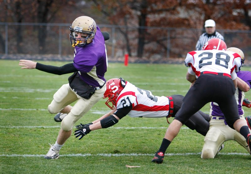 Cheverus quarterback Peter Gwilym zips past a dive by Kellen Smith of Scarborough during a first-half run Saturday.