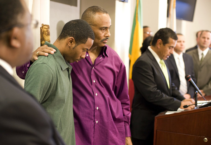 Aaron Shannon Sr., left, is comforted by his father, William, during a police news conference in Los Angeles Friday. Two alleged gang members were arrested Friday in 5-year-old Aaron Shannon Jr.'s killing. Shootings of children in misdirected gang gunfire have become rare.