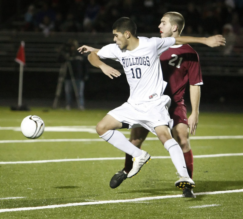 Fazal Nabi of Portland looks to get to the ball ahead of Adam King of Bangor during Bangor's 3-2 victory Saturday in the Class A boys' soccer state final at Falmouth.