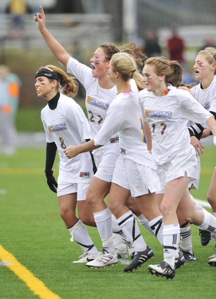 Jessica DiPhilippo of Falmouth raises her arm and celebrates with teammates Saturday after scoring the penalty kick that gave the Yachtsmen the Class B state championship.