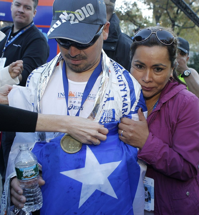 Angelica Alvarez, right, the wife of Chilean miner Edison Pena, embraces her husband after he crossed the finish line of the New York City Marathon on Sunday. Pena said training for the race in darkness during his 69 days underground was his salvation.