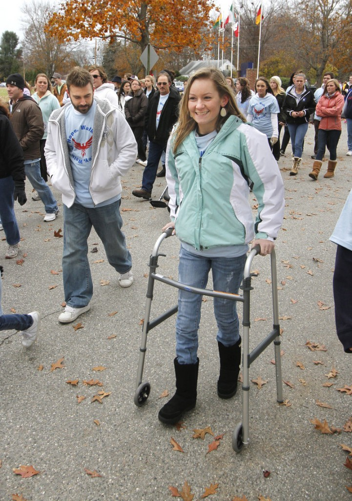Ashley Dubois demonstrates her recovering mobility as she finishes a walk organized for her benefit in Kennebunk on Sunday. The event raised an estimated $17,000 to help with Dubois' ongoing medical expenses following a car accident in September. Local businesses donated money and raffle items for the walk, which was conceived and organized by some of Dubois' classmates.