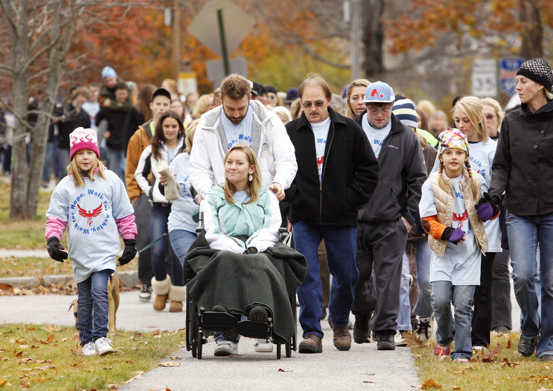 Hundreds of people participate in a walk in Kennebunk on Sunday in support of high school senior Ashley Dubois, who was injured in a car crash in September. Ashley, whom doctors doubted would walk again, started and ended the event walking with a metal walker. For most of the route, she led the way in a wheelchair pushed by her brother Matt Dubois.