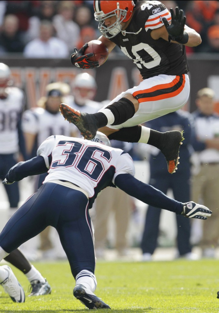 Cleveland running back Peyton Hillis leaps over New England safety Josh Barrett during the Browns' dominating 34-14 victory Sunday in Cleveland. Hillis rushed 29 times for 184 yards and two touchdowns.