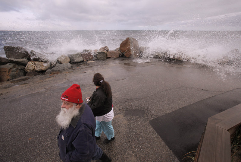 Marcel and Lori Morin of Saco walk down Eastern Avenue in Camp Ellis as water sprays over a sea wall Monday. Damage in southern Maine was said to be widespread, but minor.