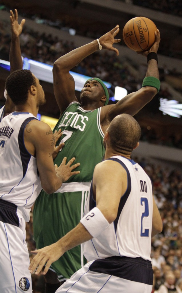 Boston's Jermaine O'Neal takes a shot over Dallas' Tyson Chandler, left, and Jason Kidd during the first half of their game Monday night in Dallas. The Mavs won, 89-87.