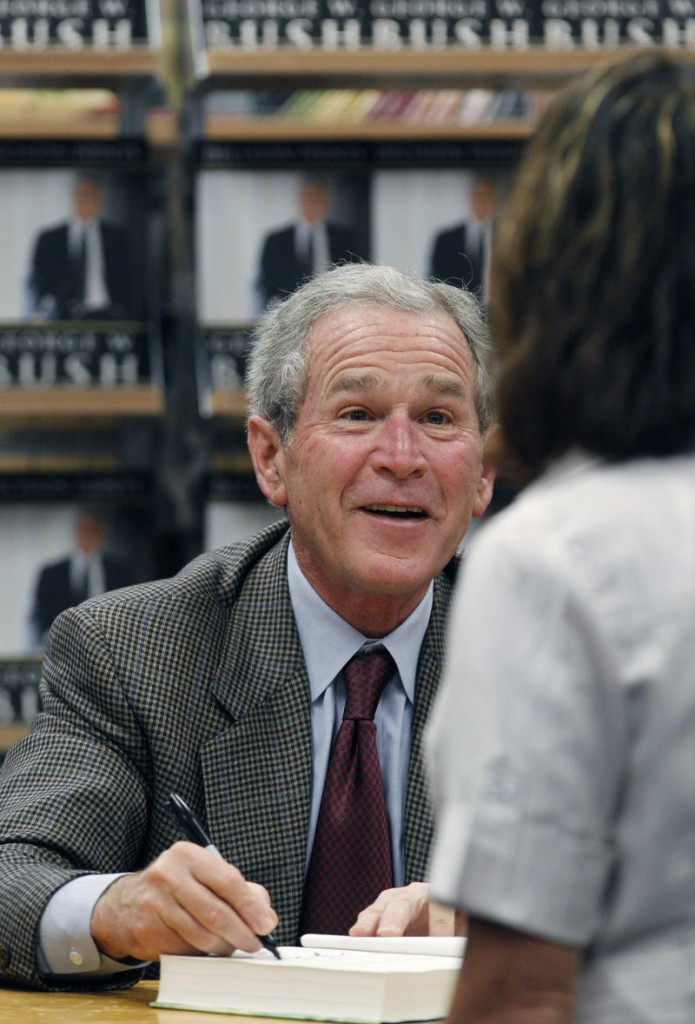 "Former President George W. Bush signs a copy of his book ""Decision Points"" at a bookstore in Dallas on Tuesday. A long line of fans gathered earlier to get an autographed copy."