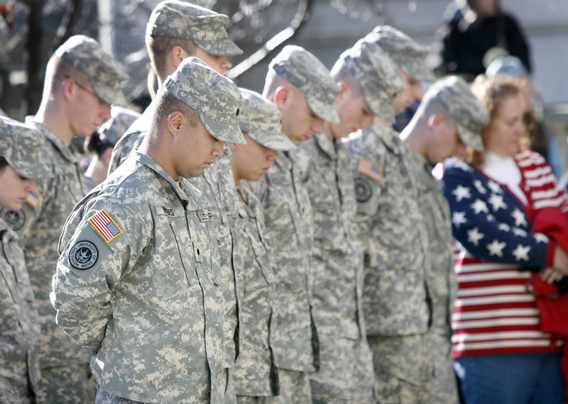 Members of the University of Southern Maine Army ROTC, who helped lead the parade, bow their heads during the playing of taps after the laying of the wreaths ceremony at City Hall.