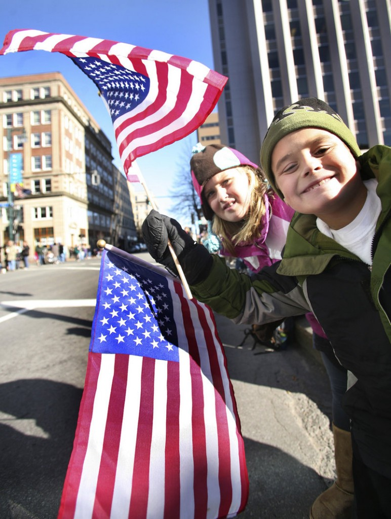 Emma Letarte, 9, and Sam Letarte, 8, who live in Scarborough, take a look down Congress Street in Portland on Thursday, hoping to see evidence that the Veterans Day parade has begun.