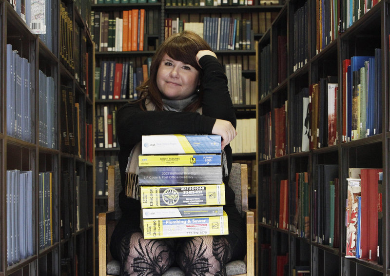 Emily Goodmann sits with a stack of phone books, the subject of her dissertation as a doctoral student, in the Northwestern University Library in Evanston, Ill. Goodmann says white pages directories should be archived for historical purposes.