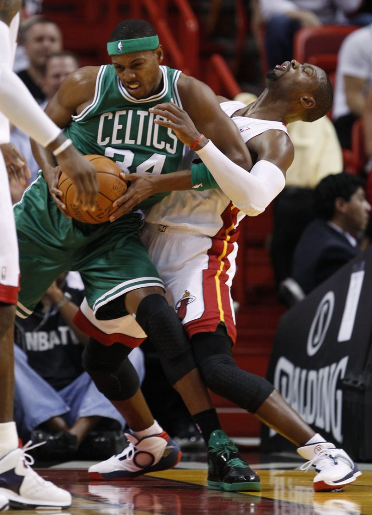 Paul Pierce of the Boston Celtics is called for an offensive foul as Dwyane Wade of the Miami Heat takes the charge in the first quarter of Boston's 112-107 victory Thursday.