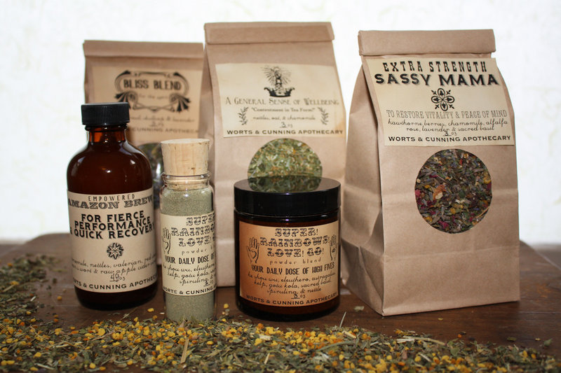Worts & Cunning Apothecary herbal products include Bliss Blend tea, A General Sense of Wellbeing tea, Sassy Mama tea, Empowered Amazon Brew vinegar, and Super! Rainbows! Love! Go! herbal powder.