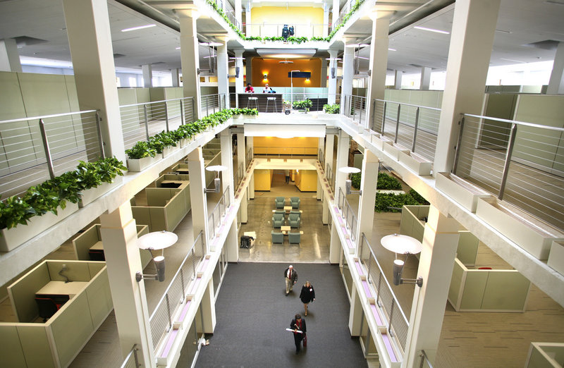 MaineHealth employees walk through the atrium during a tour of their new office space at 110 Free St. on Friday. The building formerly housed a Sears store and offices of Blue Cross and Blue Shield of Maine.