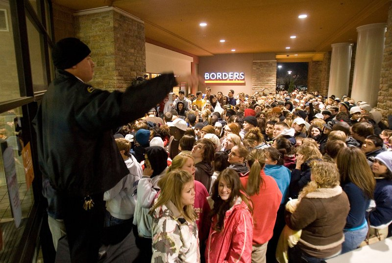 "A security guard tries to keep people in an organized line minutes before opening the front doors at a Boise, Idaho, mall on Black Friday in 2007. Sale plans are increasingly being leaked to the public about the post-Thanksgiving shopping ""holiday."""