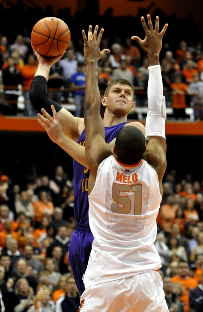 Austin Pehl of Northern Iowa lifts a shot over Fab Melo of Syracuse during the first half of Syracuse's 68-46 victory Friday night in a college basketball opener.