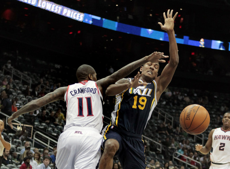Utah Jazz guard Raja Bell is fouled by Atlanta Hawks guard Jamal Crawford during Friday night's game in Atlanta. The Jazz came back to win from a double-digit, second-half deficit for the fourth straight game.