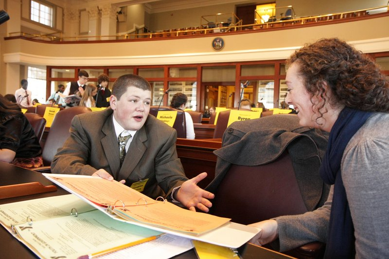 Winthrop High School sophomore Cameron Armstrong discusses a bill with Allyson Carmichael of Houlton High School in the State House chambers Saturday in Augusta. Armstrong was one of two Winthrop students taking part in this weekend's Maine Youth in Government program.