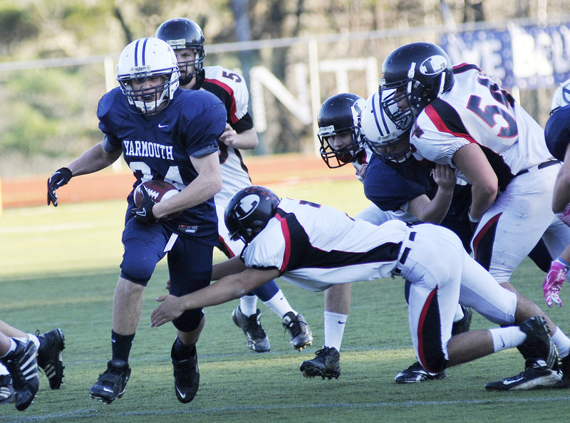 Anders Overhaug, who gained 109 yards on 15 carries for Yarmouth, attempts to slip past Mike McNamara of Lisbon during their Western Class C championship game Saturday at Yarmouth High. Yarmouth won 14-12 and will play Stearns for the state championship next Saturday in Portland.